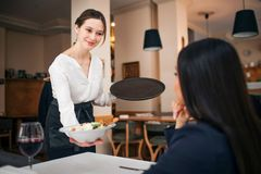 Pleasant young waitress stand at table with sitting customer and show her bowl of salad. She smiles. Female customer royalty free stock images