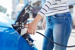Pleasant young woman holding a car charger Royalty Free Stock Photography