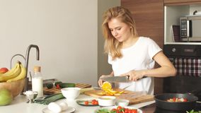 Pleasant young woman preparing dinner in a kitchen concept cooking. Pleasant young woman preparing dinner in a kitchen. Concept of healthy home cooking stock video