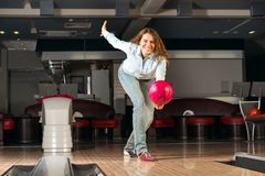Pleasant young woman throws a bowling ball. Looks at the target and smiling Stock Photos