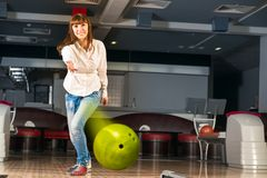 Pleasant young woman throws a bowling ball Stock Images