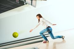 Pleasant young woman throws a bowling ball Stock Photo