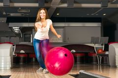 Pleasant young woman throws a bowling ball Stock Photos