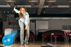Pleasant young woman throws a bowling ball Royalty Free Stock Photography