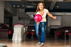 Pleasant young woman throws a bowling ball Stock Image