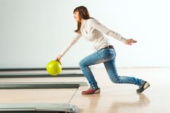 Pleasant young woman throws a bowling ball Royalty Free Stock Images