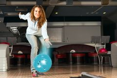 Pleasant young woman throws a bowling ball Royalty Free Stock Photos