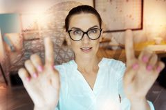 Pleasant young woman touching interactive screen with two fingers. Interactive technology. Pleasant young woman in eyeglasses raising two fingers and touching an Stock Photography