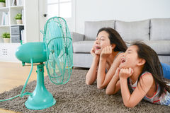 Pleasantly mother with young little daughter. Lying down on living room floor and face to electric fan enjoying blowing cool wind together at summer royalty free stock images