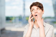 Pleasantly shocked woman with mobile phone. In the office Stock Photography