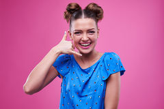 Pleasantly smiling model gesturing call me. Close-up of pleasantly smiling model gesturing call me isolated over pink background. Funny female with two buns royalty free stock photo