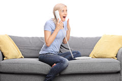 Pleasantly surprised girl talking on the telephone. Seated on a gray sofa isolated on white background royalty free stock images
