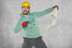 Pleasantly surprised worker indicates a construction plan. Protective helmet on the head royalty free stock image