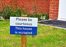 Please be courteous - This house is occupied. Sign on sold house displaying please be courteous - this house is occupied Stock Photo