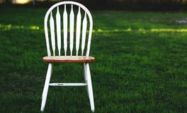 Please Be Seated. Closeup shot of a wooden chair set on a green grass lawn waiting for someone to take a seat Royalty Free Stock Photo