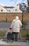 Please call again. Old lady with shopping trolley and walking stick Royalty Free Stock Image
