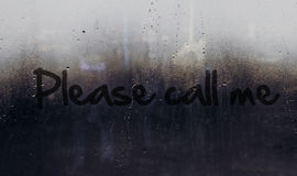 Please call me message written on car or building window. Please call me message in wet rained dark glass Royalty Free Stock Image