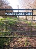 Please close gate sign on metal closed gate outside country way. Essex; england; uk royalty free stock photography