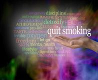 Please consider quitting smoking word cloud. Male hand with the words QUIT SMOKING floating above surrounded by a relevant word cloud with a vibrant modern stock photography