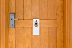 Please do not disturb sign on Closed wooden door of hotel room royalty free stock photography