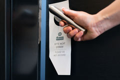 Please do not disturb sign on a room door. Room service - someone ignore the please do not disturb sign on the door handle of door of a room at the hotel Stock Image