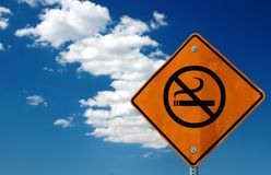 Please don't smoke. Yellow street sign with no smoking symbol with clear blue sky background Stock Image