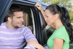 Please, drive safe!. Attractive young women holding the hand of her boyfriend ready to go on the car Royalty Free Stock Images