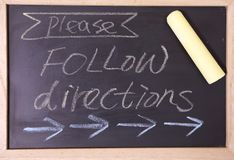 Please follow direction blackboard. Sign. please follow direction written with chalk on black chalkboard with frame Stock Photo