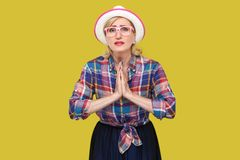 Please forgive me. or give me one more chance, Portrait of hopeful mature woman in casual style with hat and eyeglasses standing royalty free stock photography