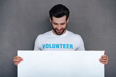 Please help to community!. Confident young man in volunteer t-shirt holding white board and looking at it with smile while standing against grey background Royalty Free Stock Image