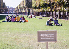 Please Keep Off the Grass, Luxembourg Garden, Paris, France. Sign 'Pelouse Interdite' (keep off the grass) in foreground; groups of people sitting on the grass stock image