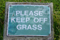 Please Keep Off Grass Sign. A dirty, old sign asking people to please keep off grass. Could have a douple meaning as a funny marijuana reference Stock Photo