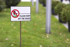 Please keep off the grass sign on green lawn grass blurred bokeh background on sunny summer day. City lifestyle and nature royalty free stock image