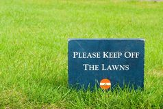 Please keep off the lawns � stone sign in the park royalty free stock image