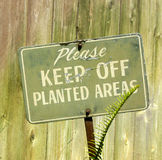 Please Keep Off Planted Areas. An old, rusted sign telling people to stay off the planted areas stock photography