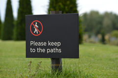 Please keep to the paths sign. Modern sign on lawn informing to please keep to the paths Stock Images