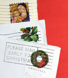 Please mail early for Christmas. Three stamped Christmas card envelopes with a postoffice reminder to mail early Royalty Free Stock Photo