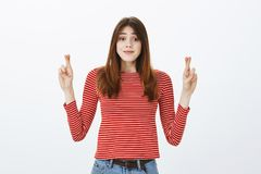 Please make my dream come true. Portrait of grinning hoping good-looking woman in striped clothes, raising hands with. Crossed fingers and smiling while wishing Royalty Free Stock Image
