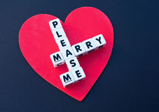 Please marry me. Large red heart on black with text 'please marry me' inscribed in uppercase letters on small white cubes and arranged jigsaw style with common Royalty Free Stock Photography
