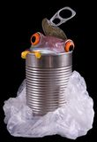 Please recycle. A red-eyed tree frog is peeking out of a discarded metal can surrounded by a plastic bag Stock Photos