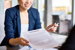Please Sign Here. Close-up shot of smiling young white collar worker passing contract and pen to business partner during productive negotiations royalty free stock image