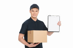 Please sign here to get your box. Cheerful young deliveryman hol Stock Image