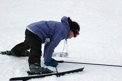 Please someone help me!. Skier fell down and is having hard time to get up royalty free stock photo