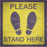 PLEASE STAND HERE foot sign or symbol on the floor Royalty Free Stock Images