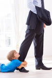 Please stay!. Sad little boy embracing his father leg and looking up while lying on the floor royalty free stock images