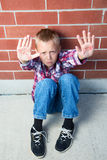 Please Stop. A pre-teen boy is begging to stop doing something bad showing a message written on his palms royalty free stock images