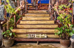 Please take off your Shoes wooden Sign. Frontal view of wooden stairs with a Please take off your Shoes sign Royalty Free Stock Photos