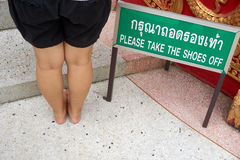 Please take the shoes off label with woman leg Royalty Free Stock Photos