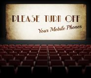 Please turn off cell phones movie screen in old cinema. Please turn off cell phones movie screen concept in old retro cinema Royalty Free Stock Photo