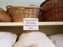 Please unload the wagon when you are done sign on shelf. With bags and baskets stock photography